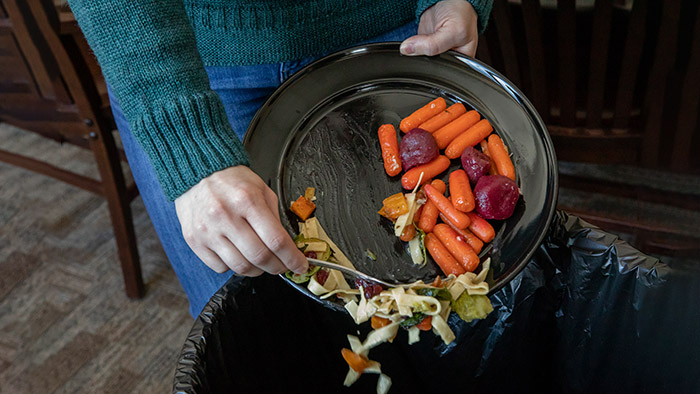 Food waste being scraped into garbage can from plate.