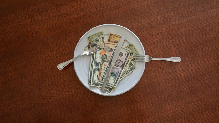 Money displayed on a dinner plate with silverware.